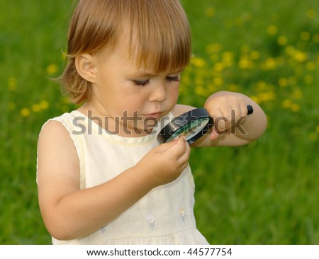 Cute child looking at little snail through magnifying glass - stock photo