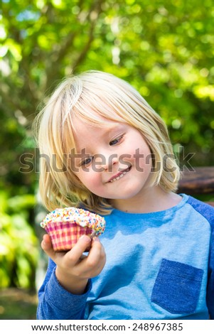 Cute child looking at tempting cupcake treat for a snack - stock photo