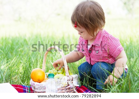 Cute child on a picnic, eating a big fresh apple - stock photo
