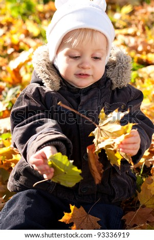 Cute child played by maple leaves. Golden autumn nature blurred background - stock photo