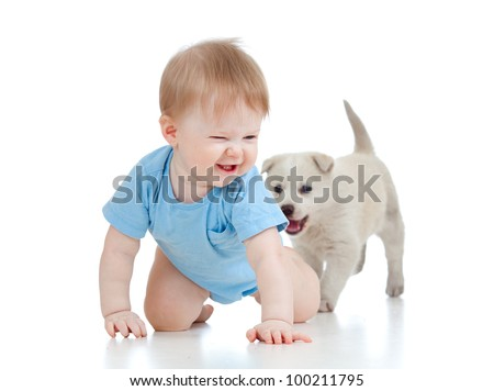 cute child playing and crawling away a puppy, puppy following - stock photo