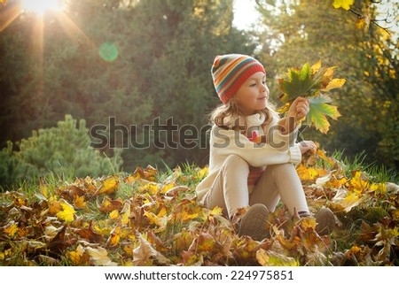 Cute child playing with autumn leaves - stock photo