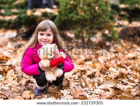 Cute child playing with her toy in autumn leaves in park outdoor  - stock photo