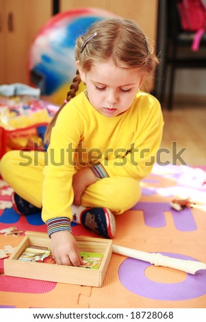 Cute child playing with puzzle - stock photo