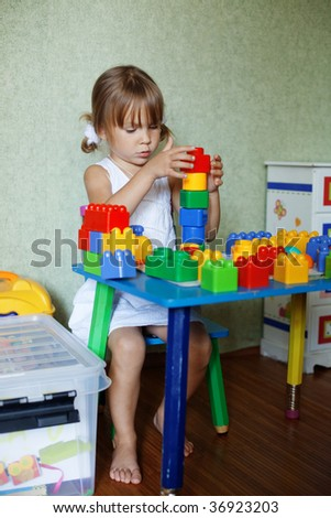 Cute child playing with the constructor bricks at home