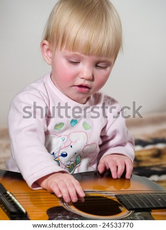 cute child plays on guitar