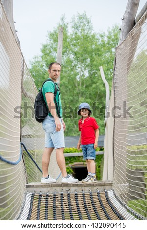 Cute child, preschool boy, climbing in a rope playground structure with his father, springtime. Fathers day concept