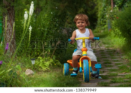 cute child riding his trike in the garden - stock photo