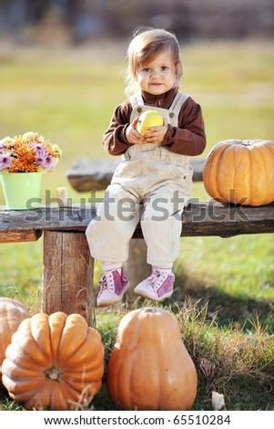 Cute child sitting on bench near pumpkins - stock photo