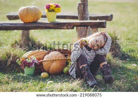 Cute child sitting on grass near pumpkins - stock photo