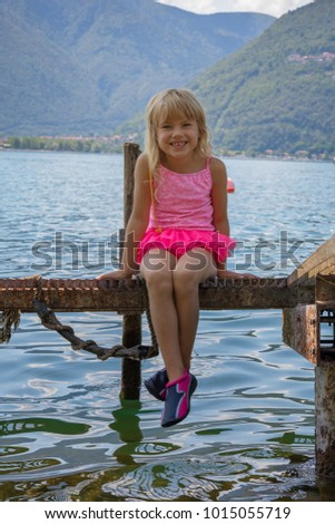 cute child sitting on the jetty during family vacation at the Lago Maggiore in Italy