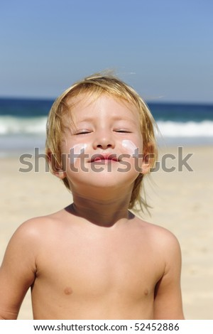 cute child sunbathing with sunscreen in her face at the beach smiling - stock photo