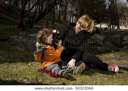 Cute child taking pictures of his mother - stock photo