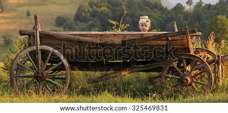 Cute child wearing a traditional cap looking from a wooden rustic cart