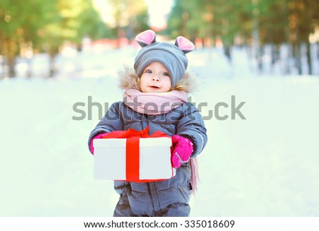 Cute child with christmas box gift in winter day - stock photo