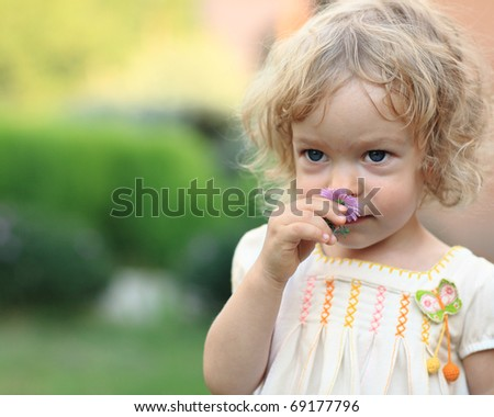 Cute child with flower in spring garden - stock photo