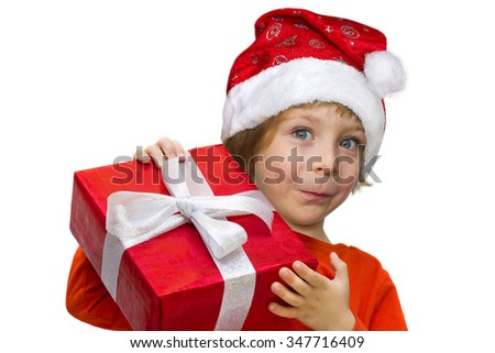 Cute child with Santa hat, blue eyes, blond hair, smiling, dressed in a red shirt holding a red wrapped present box with silver ribbon close-up portrait isolated on white background