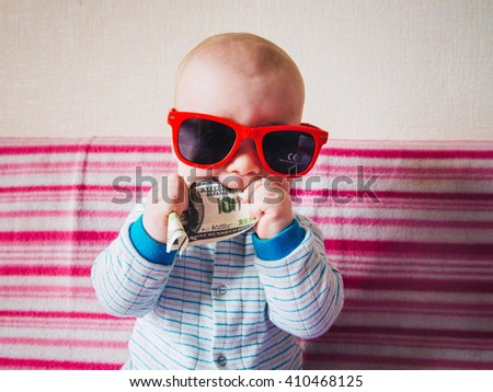 cute child with sunglasses holding dollars and chomping - stock photo