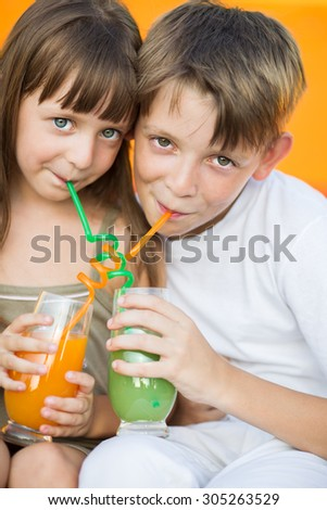 cute children drinking orange juice in the summer outdoors