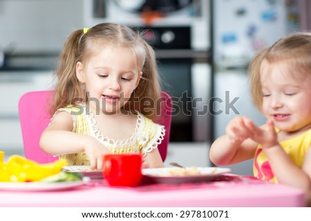 Cute children eat healthy food in nursery or at home
