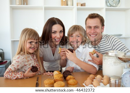 Cute children eating muffins with their parents in the kitchen - stock photo