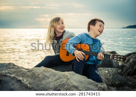 Cute children having a lot of fun with guitar by the sea - stock photo