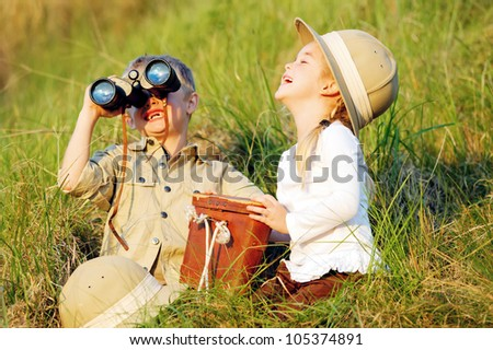Cute children having fun and laughing together outdoors with binoculars and safari hats - stock photo