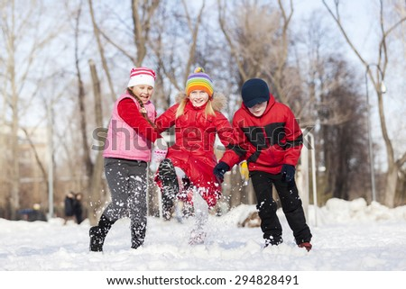 Cute children jumping and having fun in winter park - stock photo