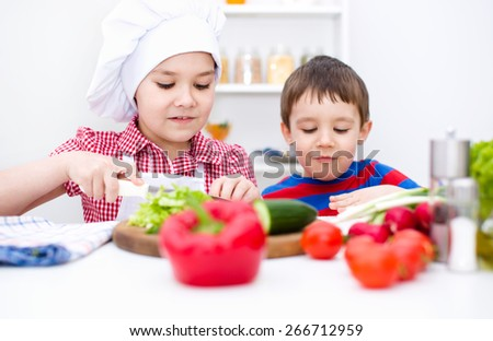 Cute children make vegetable salad