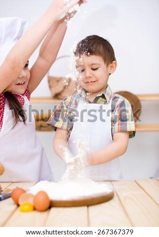 Cute children making bread in the kitchen - stock photo