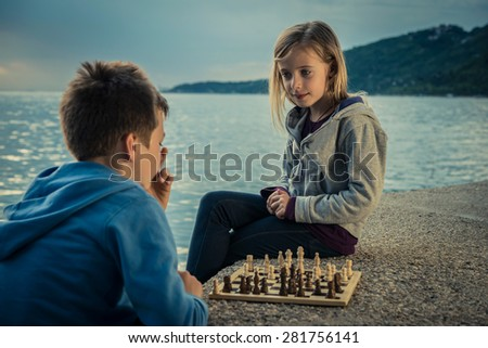 Cute children playing chess by the sea - stock photo