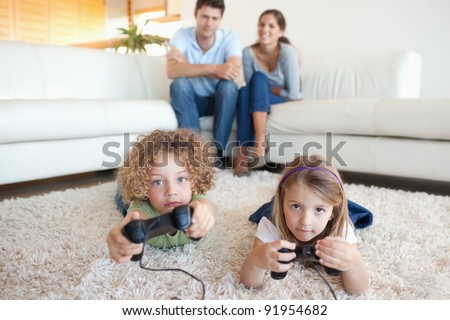 Cute children playing video games while their parents are watching in their living room - stock photo