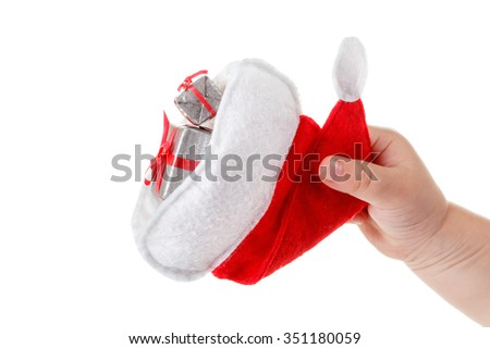 Cute children's hand holds a santa hat and christmas gifts. Isolated on white background - stock photo