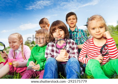 Cute children sitting on grass with magnifier - stock photo