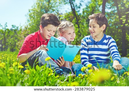 Cute children with book reading and talking on lawn
