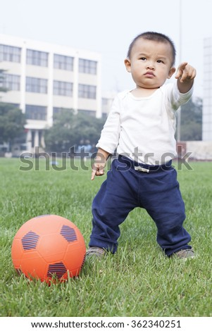 Cute Chinese baby boy playing soccer in meadow, shot in Beijing, China - stock photo