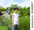 Cute Chinese boy outdoor in white shirt (in front of waterfall) - stock photo