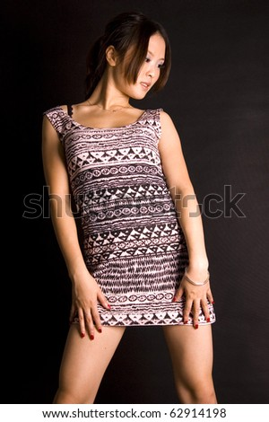 Cute Chinese teenager wearing short skirt, young and fashionable. Pretty Asian female model with black background.