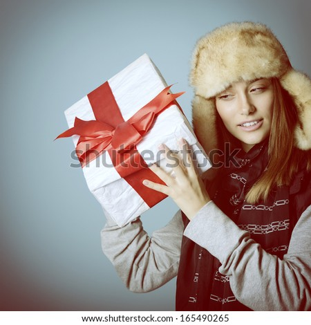 """Cute christmas girl in winter hat holding gift box and try to guess right """"what is inside"""", over blue, toned - stock photo"""