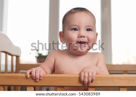 Cute chubby baby with a happy smile and alert intelligent expression standing in a wooden cot in front of nursery windows looking to the side