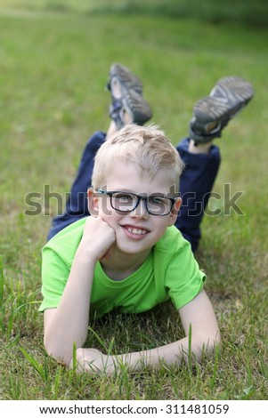 Cute clever boy in glasses lies on green grass outdoor - stock photo