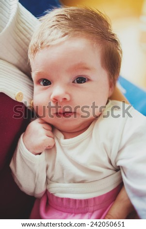 Cute close up portrait of smiling baby in mother's arms - stock photo