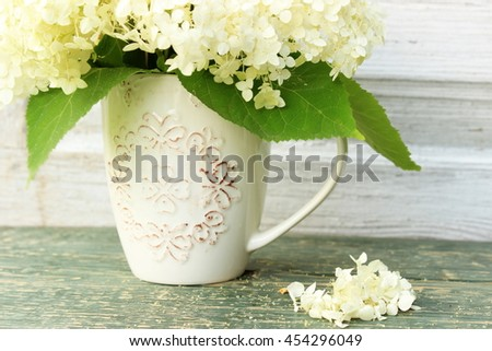 Cute composition in green and white color with bouquet of hydrangea in vintage ceramic cup on withered wooden background. Floral decor elements. Concept for greeting card. Shabby chic