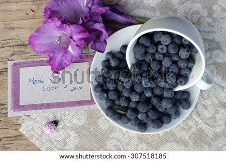 Cute composition with bilberries in a cup