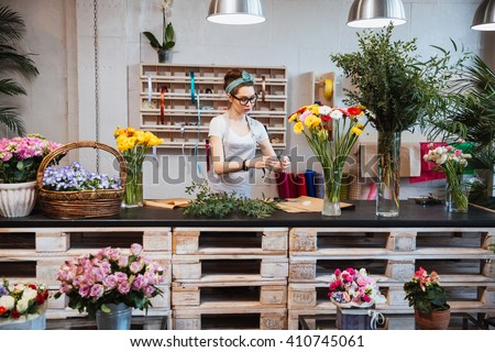 Cute concentrated young female florist in glasses working in flower shop - stock photo