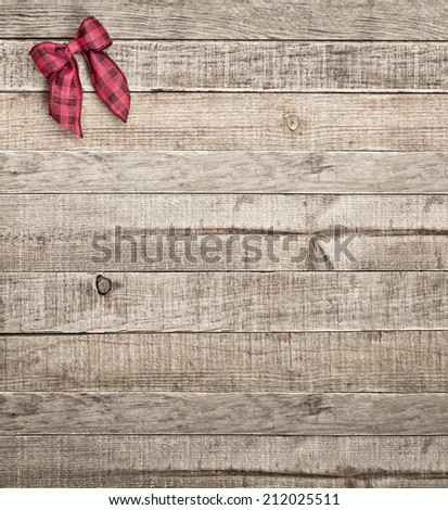 Cute Country Checked Christmas Bow on Rustic Board Background with room or space for copy, text, words.  Vintage Bleach Bypass treatment on vertical that can be cropped to horizontal - stock photo