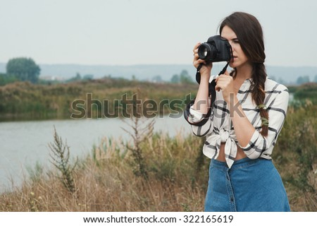 Cute countryside lady with brown hair posing against ranch house and pond with camera. She stands near tall grass and reed against rural scape. She wears jeans dress. Camera is black - stock photo