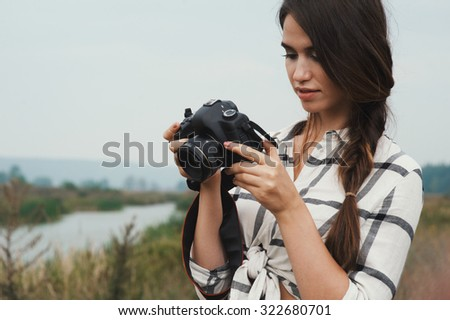 Cute countryside lady with brown hair posing against ranch house and pond with camera. She stands near tall grass and reed against rural scape. She wears jeans dress. Camera is black