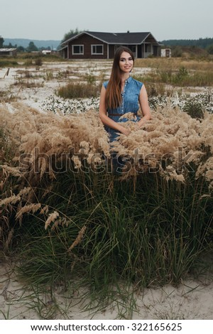 Cute countryside lady with brown hair posing against ranch house. She stands in tall grass against rural scape. She wears jeans dress. House has one floor. It is made of wood and is painted brown. - stock photo