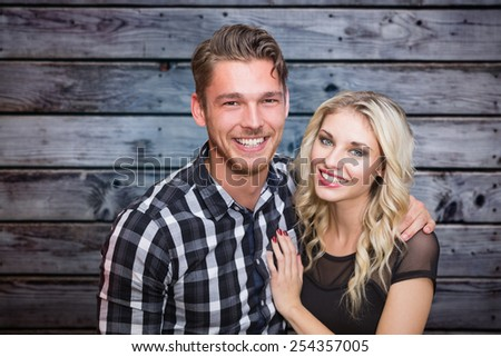 Cute couple against grey wooden planks - stock photo